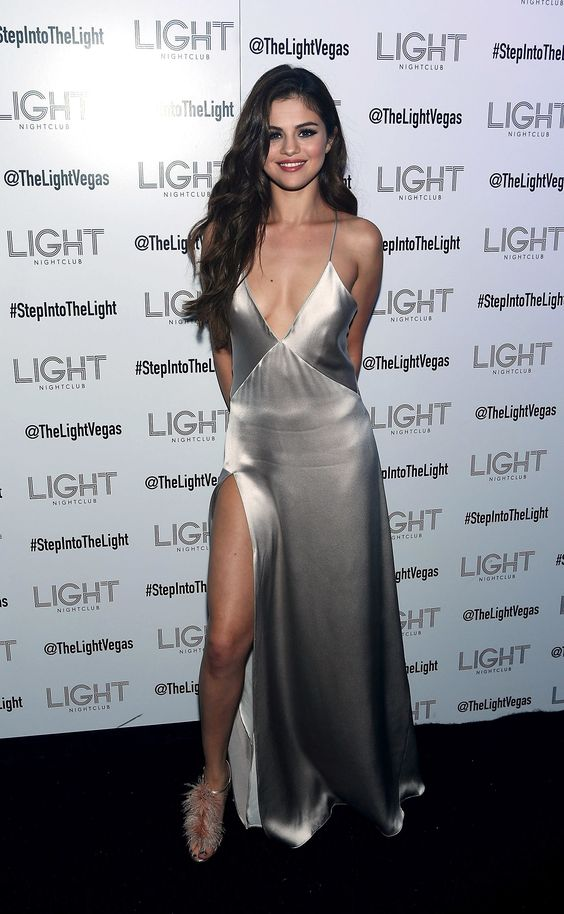 a silver slip dress with a deep V-neckline and a thigh high slit plus feather shoes by Selena Gomez