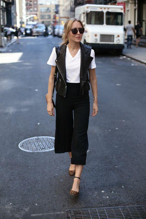 a white tee, black culottes, a black leather vest, leopard print shoes