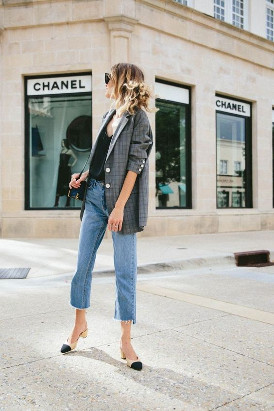 a black top, blue jeans with a raw hem, a plaid oversized blazer, black and creamy shoes
