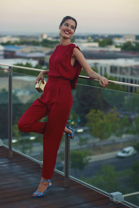 a hot red pantsuit with a cape and pearls on the shoulders, blue shoes and a tony gold clutch