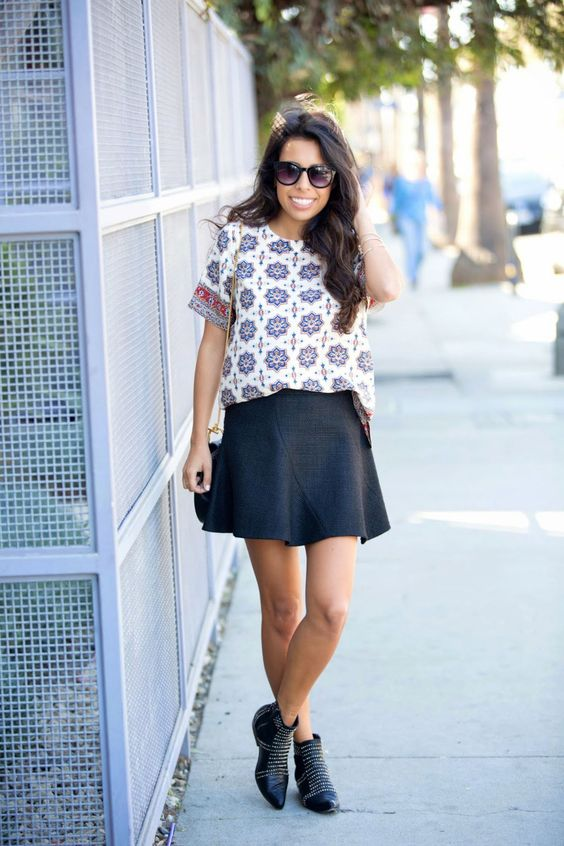 a printed tee, a structural A-line black mini skirt, black embellished boots