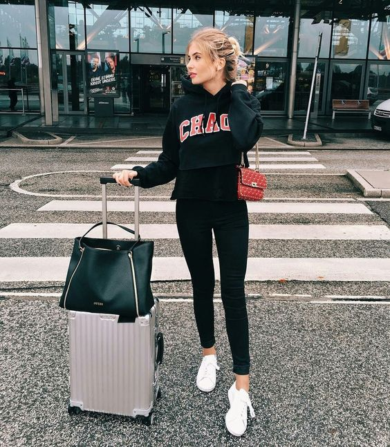 black skinnies, a black printed hoodie, a red crossbody and white sneakers for a sporty outfit