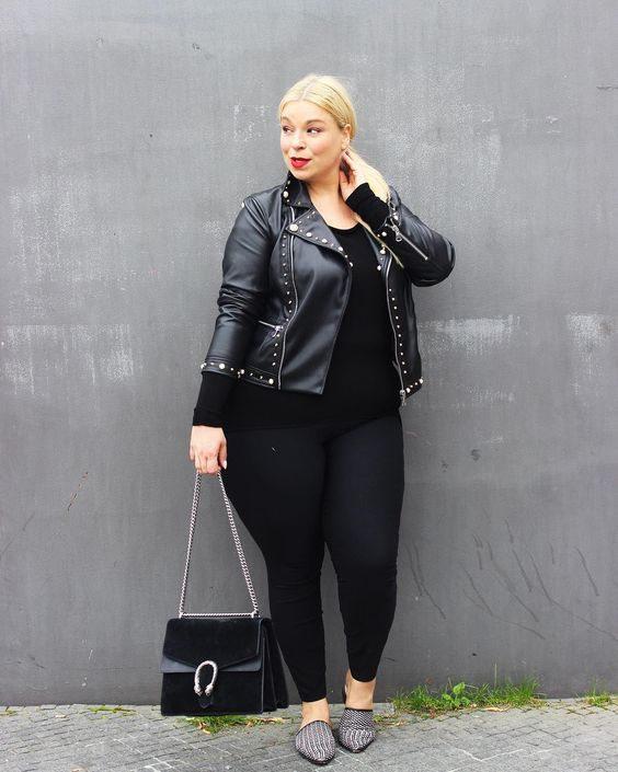 a black top, black leggings, a black leather jacket, grey printed flats and a black bag