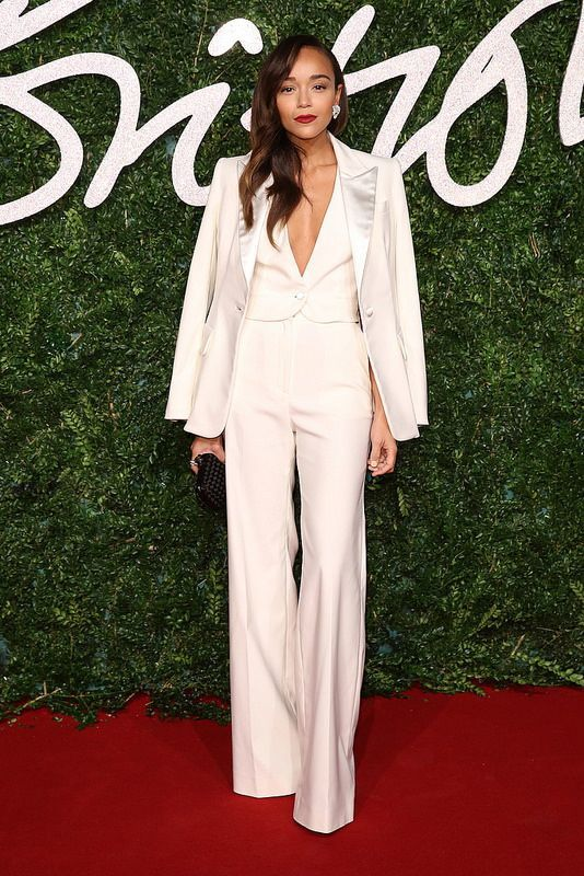a chic creamy pantsuit with a vest instead of a top, a black clutch and statement earrings for a more formal look