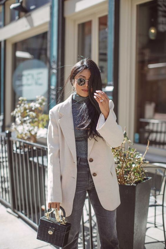 a grey turtleneck, grey jeans, a creamy oversized blazer and a small grey wicker bag