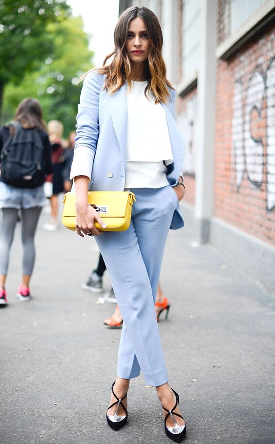 a light blue pantsuit, a white top, a yellow clutch and blakc and metallic shoes