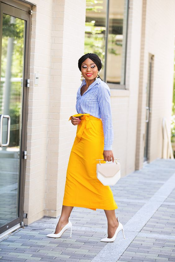 a striped blue shirt, a yellow pencil midi, white heels and a white geometric bag