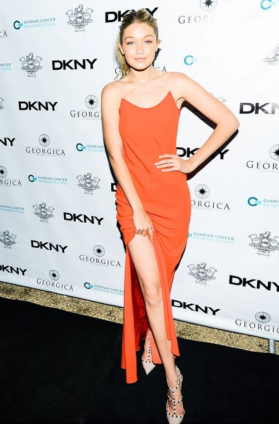 Gigi Hadid wearing an orange maxi slip dress with invisible straps and spiked shoes