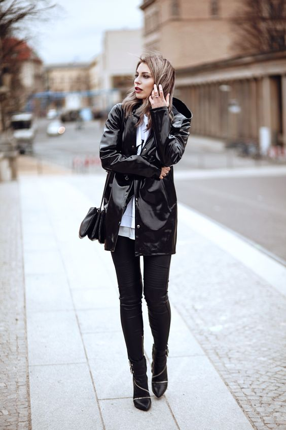 a black riancoat and black skinnies, black booties and a black bag for a chic and comfy look