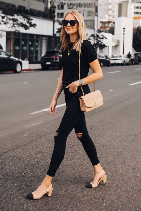 a black tee, black ripped jeans, a nude crossbody, nude and black slingback shoes