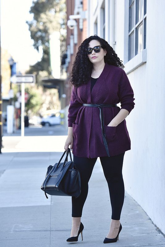 a black top, black leggings, black heels, a navy bag and a purple cardigan with a belt
