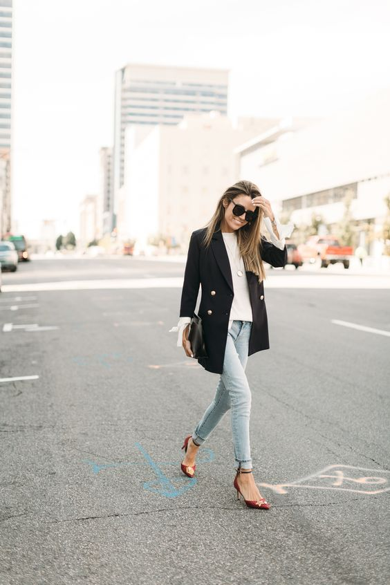 a white shirt, a black blazer with gold buttons, light blue skinnies and red shoes plus a clutch