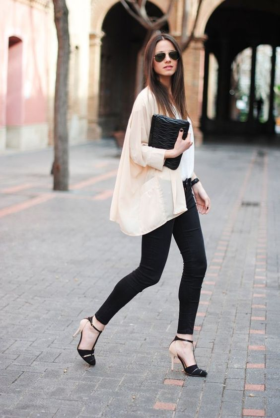 black skinnies, a white top, an airy nude shirt, black and nude shoes and a black clutch