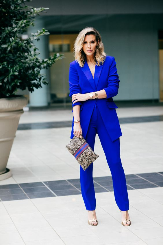 a cobalt blue pantsuit, silver shoes and a leopard with blue clutch to match