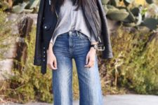 11 a grey top, blue flare jeans, an oversized black leather jacket, printed lace up shoes