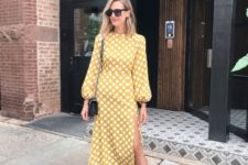 11 a mustard polka dot midi dress with catchy sleeves and a side slit, black shoes and a bag
