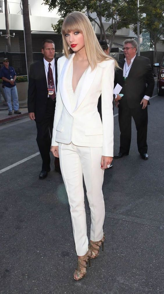 a white pantsuit with a white top with a plunging neckline underneath and gorgeous metallic shoes