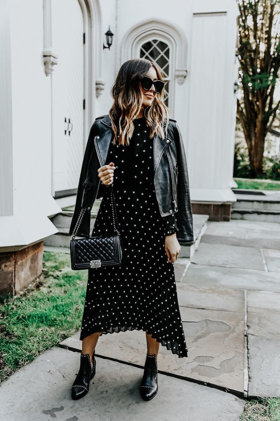 a black midi polka dot dress with a high neckline, black studded boots, a black leather jacket and a blakc bag