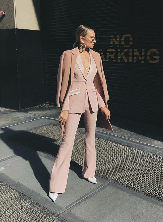 a blush pantsuit with shiny detailing, no top under and white shoes plus statement earrings