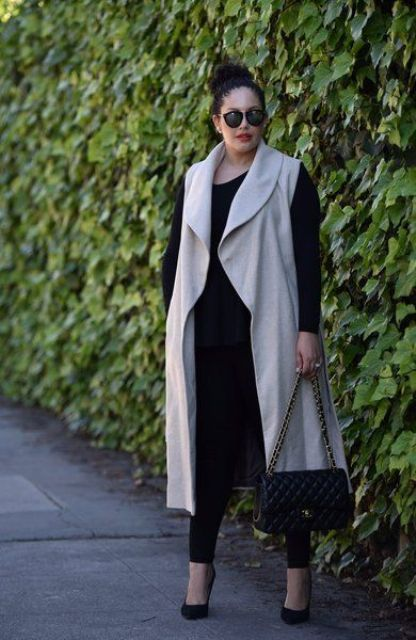 a chic look with black leggings, a black top, black heels and a bag and an off-white duster
