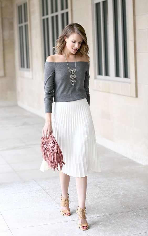 a grey off the shoulder top, a white pleated midi skirt, lace up shoes and a pink fringe clutch