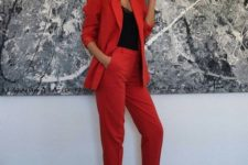 12 a red pantsuit, a black lace top, black heels and statement earrings are a bold outfit