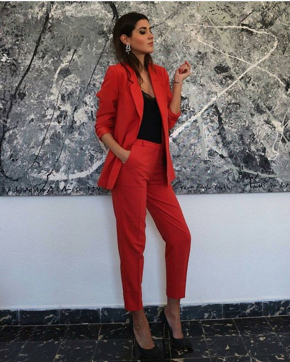 a red pantsuit, a black lace top, black heels and statement earrings are a bold outfit