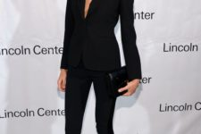 13 a perfectly tailored navy pantsuit with black stripes on the pants, black heels and a black bag