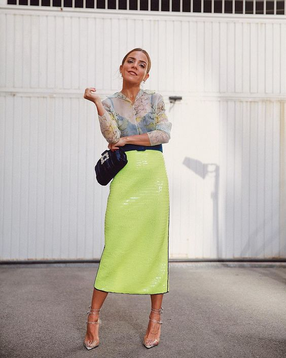 a sheer blouse, a green neon sequin midi, a black clutch and metallic shoes