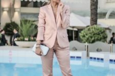 13 a soft rose pantsuit with no top on, layered necklaces, metallic shoes and a white clutch