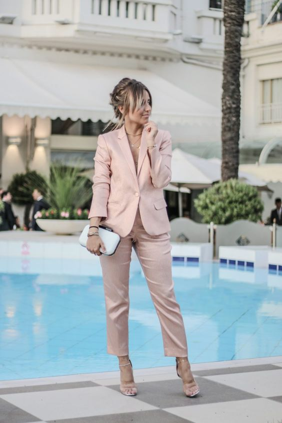 a soft rose pantsuit with no top on, layered necklaces, metallic shoes and a white clutch