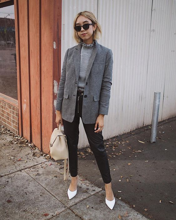 black leather pants, a grey turtleneck, a grey oversized blazer, white shoes and a creamy bag
