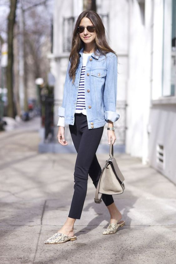 black pants, a striped top, a blue denim jacket, snake print shoes and a neutral bag