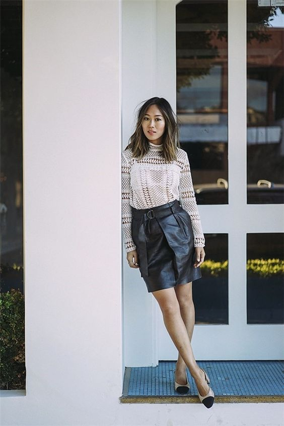 a crochet lace top with long sleeves, a black leather skirt, nude and black slingbacks