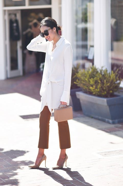 a long tie blouse, camel pants, nude heels and a nude bag for work
