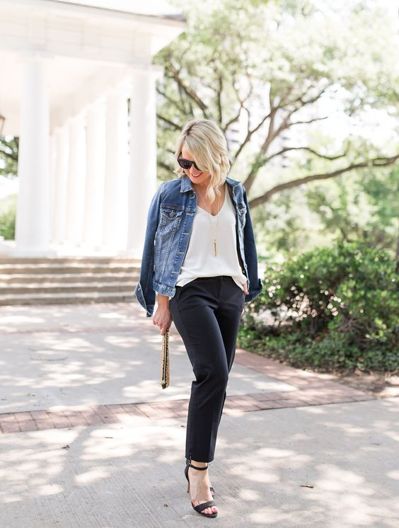 black pants, a white top, a denim jacket, black shoes and an embellished clutch