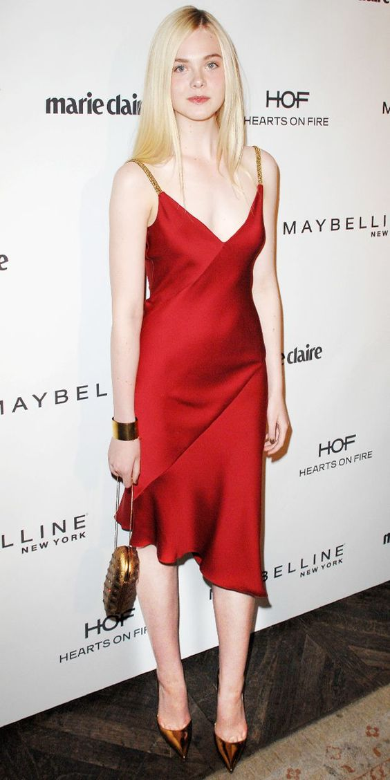 Elle Fanning wearing a red slip midi dress with an asymmetrical skirt, embellished straps, copper shoes and a clutch