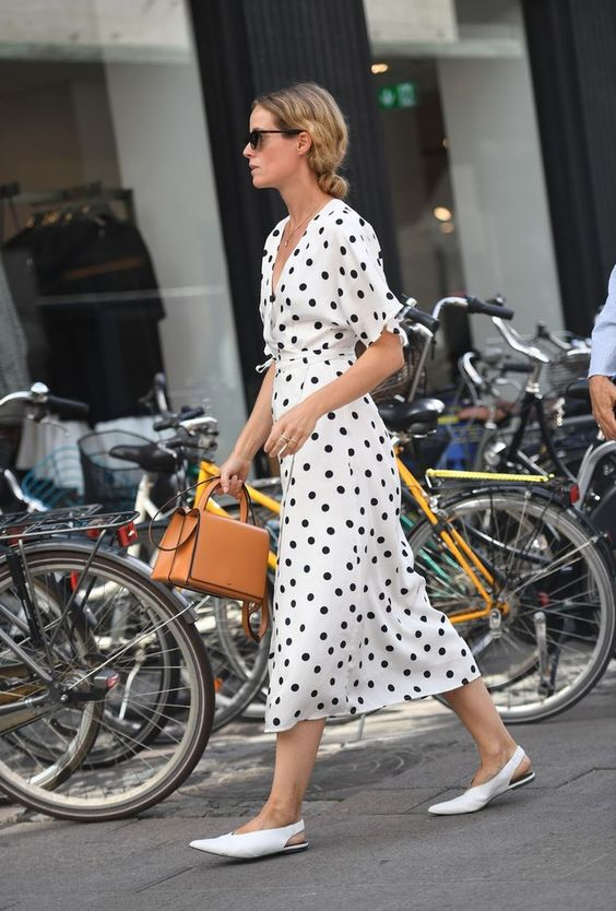 a black and white midi polka dot dress, white flats and a camel bag