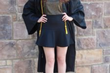 15 a black ruffled high waist skirt, a metallic top, lace up shoes and a college gown on top