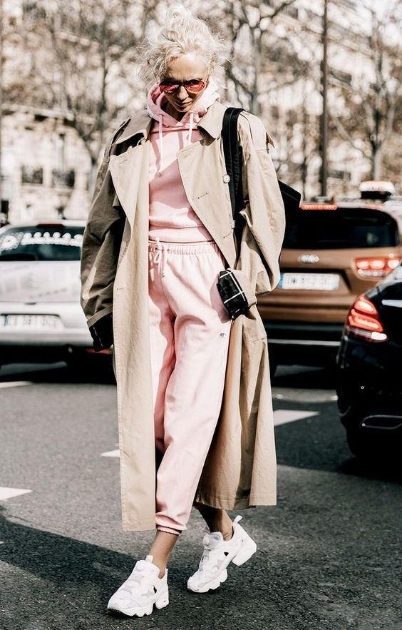a pink track suit, white trainers, an oversized beige trench and a black bag