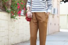 15 a striped top, cropped camel pants, black booties with high heels and a red bag