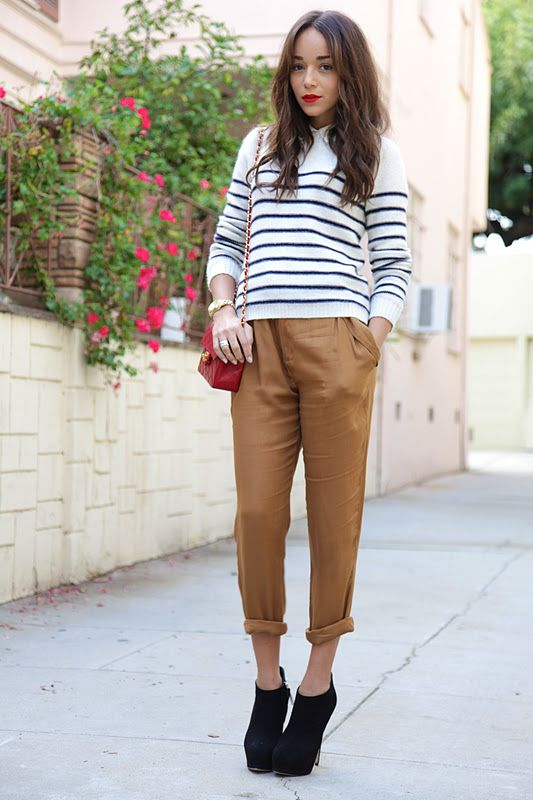 a striped top, cropped camel pants, black booties with high heels and a red bag
