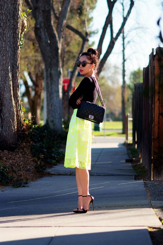 a neon yellow lace midi, a black long sleeve top, black shoes and a black Chanel bag