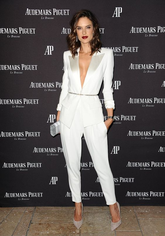 a white pantsuit with shiny lapels and no top under it, shiny shoes and a silver clutch for a statement