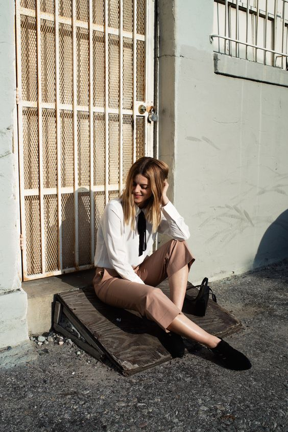 cropped camel pants, a white blouse with a black bow, black shoes and a black bag