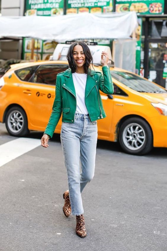 leopard print booties, blue jeans, a white tee, a green leather jacket for a bright touch