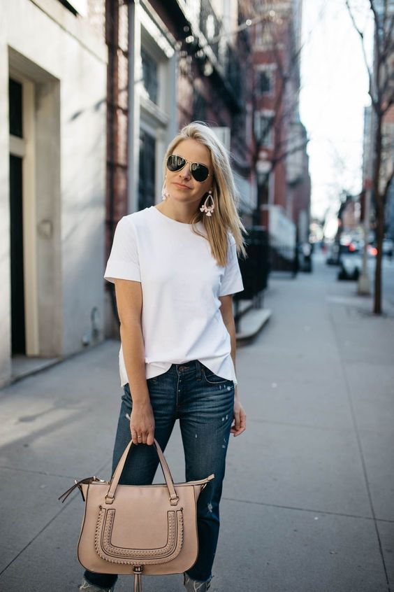 navy cropped jeans, a white tee, a blush bag and statement earrings