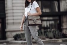 With black cap, white t-shirt, printed bag and white sneakers