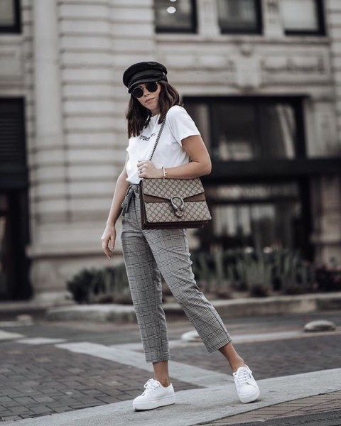 With black cap, white t shirt, printed bag and white sneakers