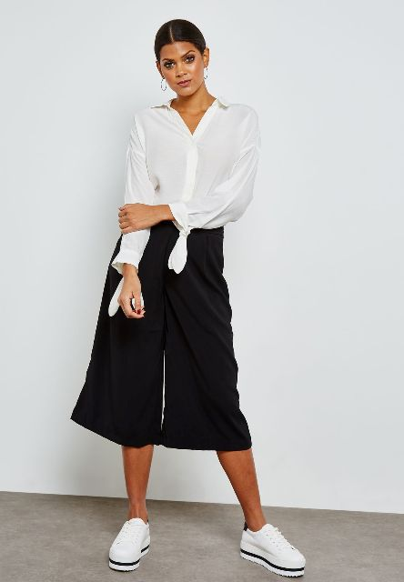 With black culottes and white platform sneakers